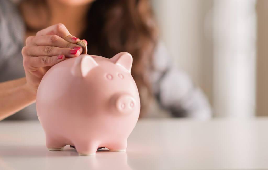 小銭を豚の貯金箱に入れる女性の手
