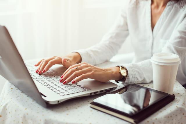 PCで固定費の見直しを行う女性の手