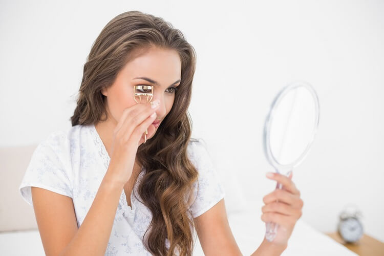 アイメイク・鏡を見ながらビューラーで睫毛をカールする女性