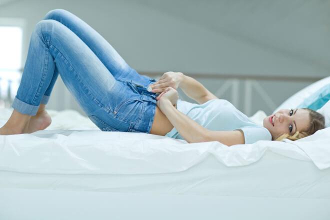 ベッドに寝転がり痩せたお腹を見せる女性
