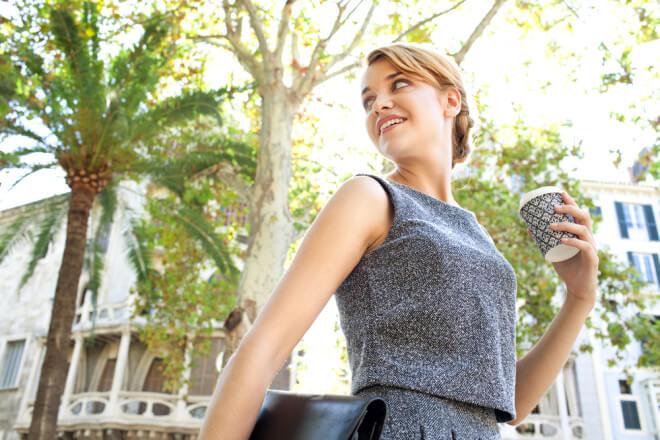バッグとコーヒーを持ち、街を歩く女性