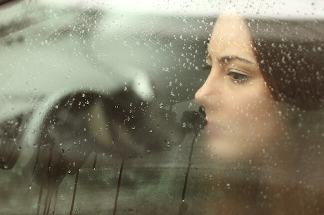 車の中から雨が降る外を眺める女性
