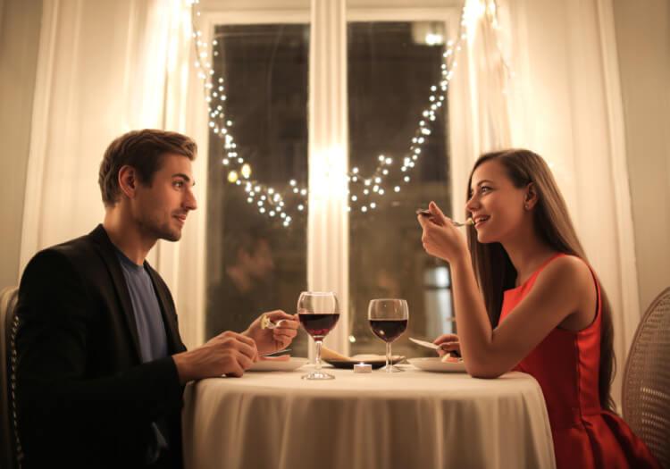 レストランで食事デートを楽しむ男女のカップル