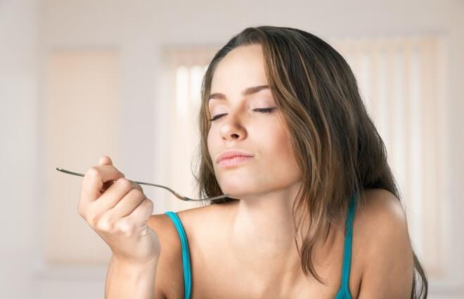 フォークを持ち食べている女性