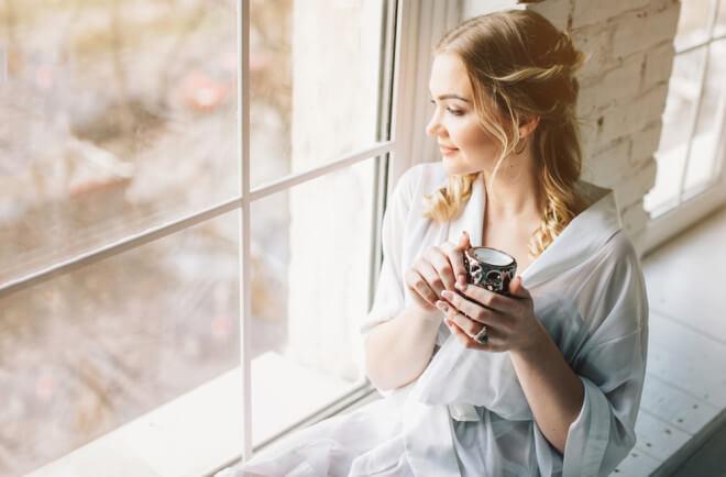 マグカップを持ち、窓から外を眺める女性