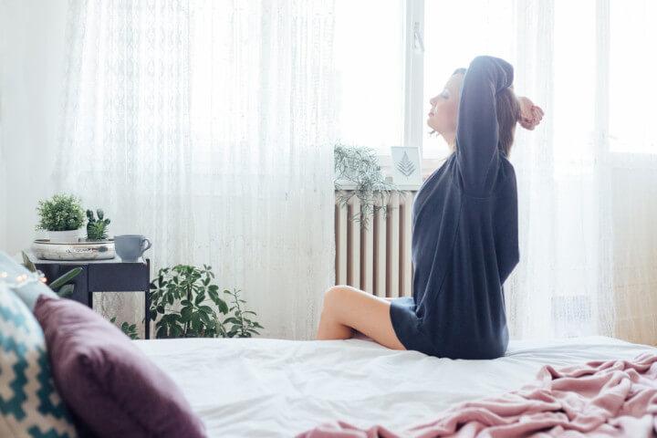 寝起きでのびをする女性