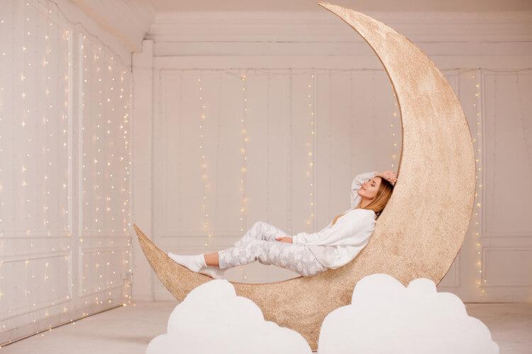 月に寄り掛かり眠るパジャマ姿の女性
