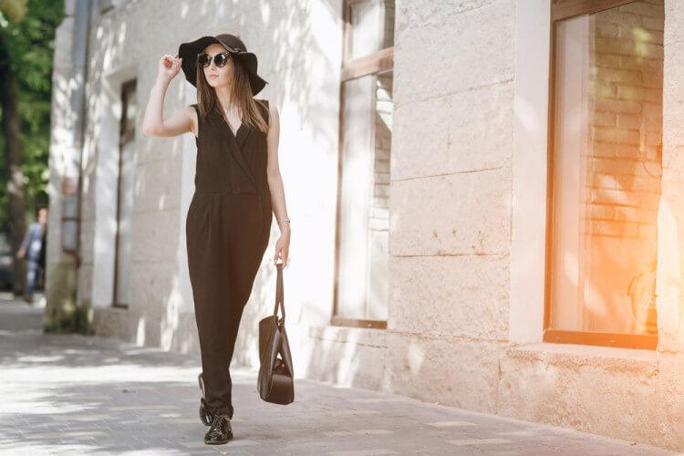 ハットを被り、サングラスをかけた女性が街を歩いている様子