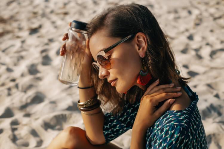 砂浜でタンブラーを持つ美女
