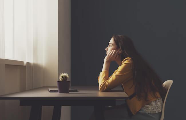 テーブルに肘をつき考え事をする女性
