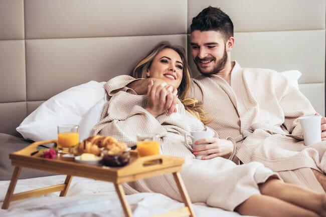 バスローブを着てベッドの上で語り合う男女