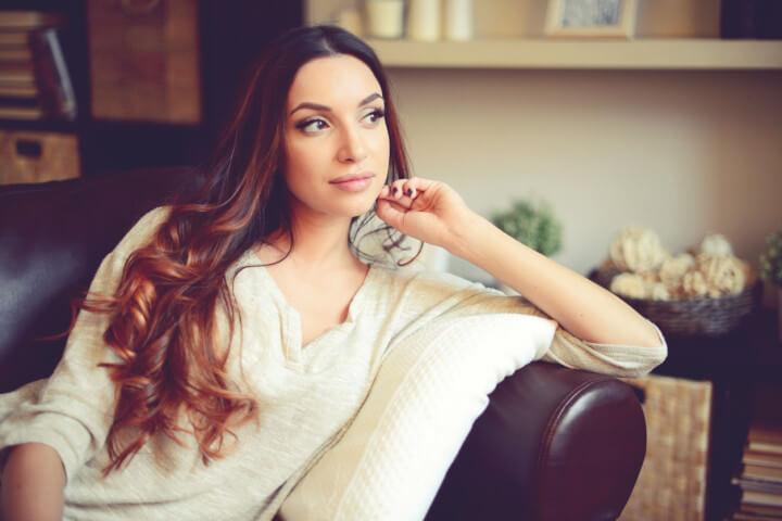 ソファーに座る巻髪の女性
