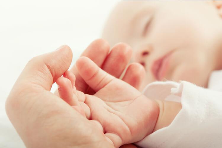 赤ちゃんの手を握る大人の手