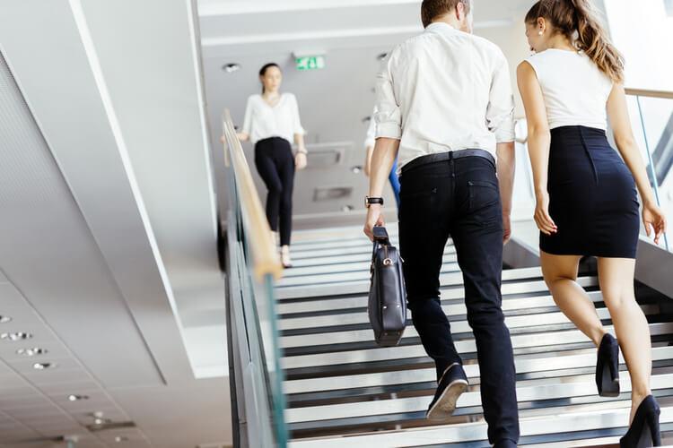 オフィスルックで階段をあがる男女