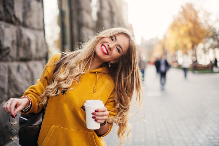 黄色のパーカーを着て外を歩く金髪美女