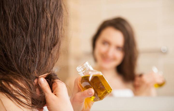 ヘアオイルをつける女性