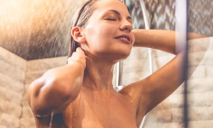 シャワーで髪を洗う女性