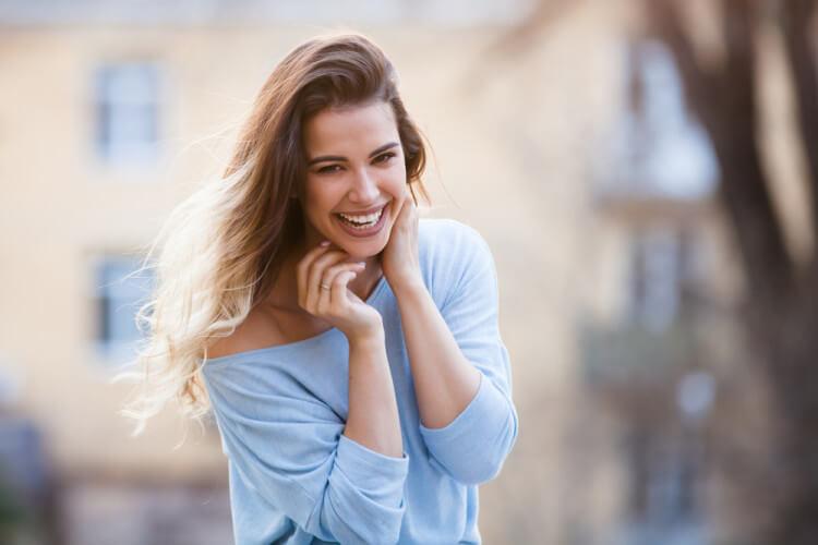 街中でブルーのニットを着た笑顔の女性