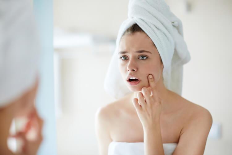 頬のニキビを鏡でチェックする女性