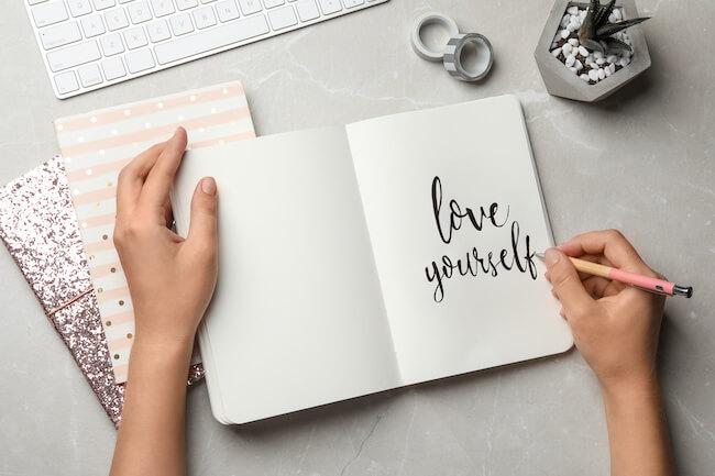 ノートにloveyourselfと書く女性の手