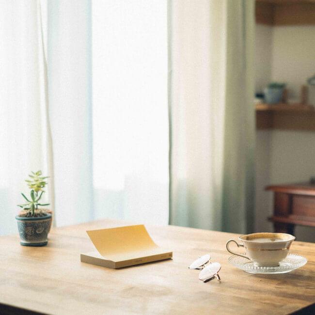 テーブルの上の本とメガネとコーヒーと植物