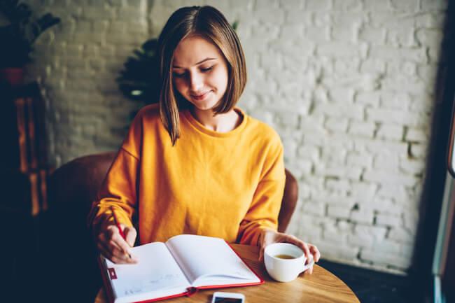 コーヒーカップを片手にノートに黄色のニットを着た書く女性