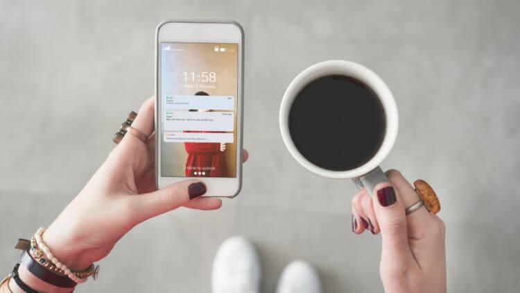 スマートフォンとコーヒーを持つ女性の手