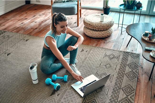 ダンベルを床に置いてノートパソコンを触る女性