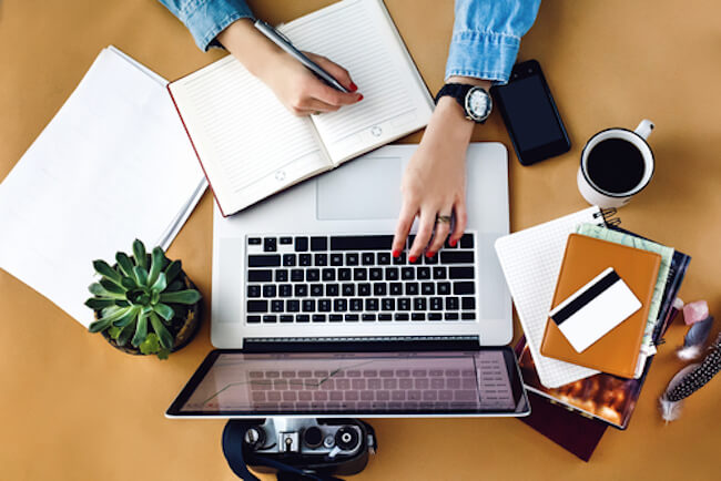 ノートパソコンのキーボードを打ちながらノートに書き込む女性の手