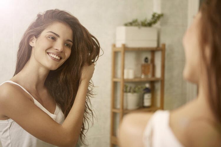 鏡を見ながら髪の毛を触っている女性