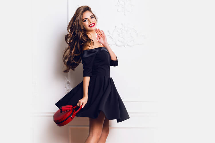 黒いワンピースに赤いバッグを持ったロングヘアの巻き髪美女