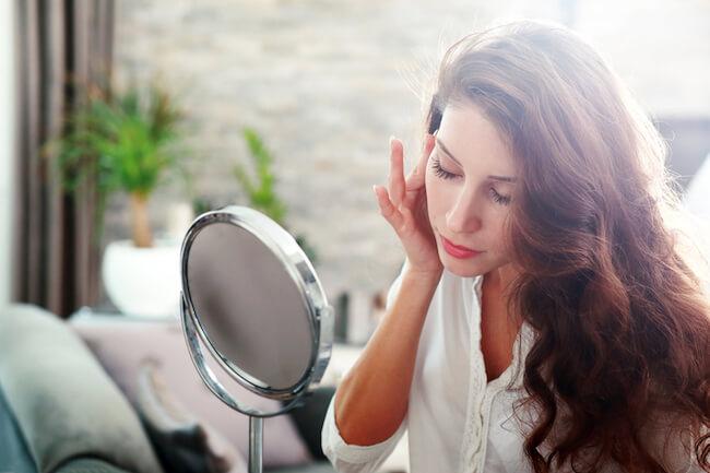 鏡を見ながら頬を触る女性