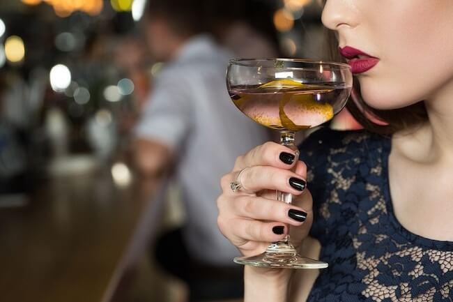 グラスに口をつける赤い口紅の女性