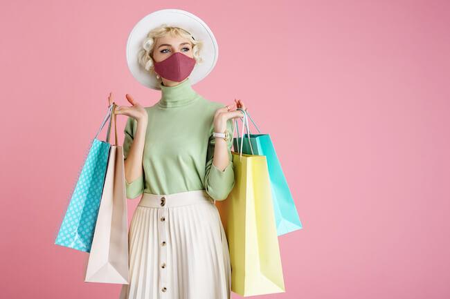 マスクをつけて両手に紙袋を持つ女性