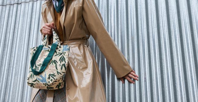 トレンチコートを着てトートバッグを持つ女性