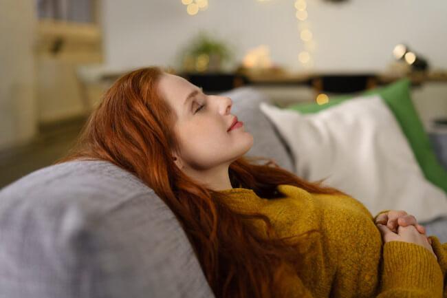 ソファーで目を閉じている美女
