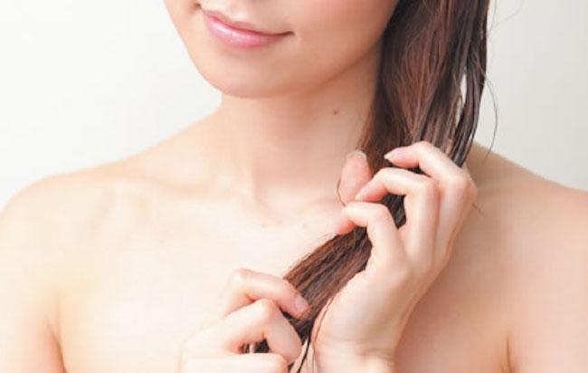 トリートメントを髪に塗る女性