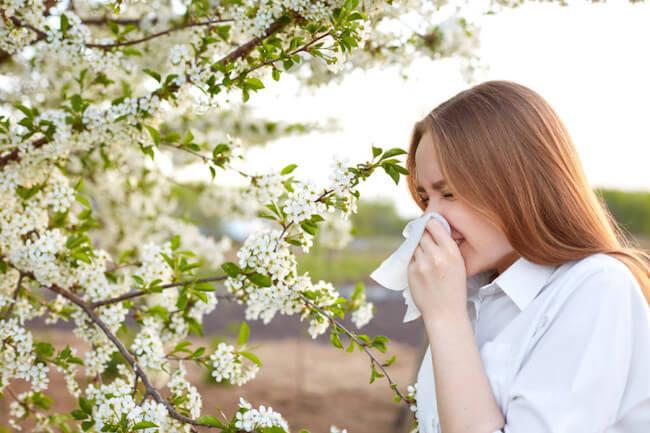 ティッシュで鼻を噛む花粉症の女性
