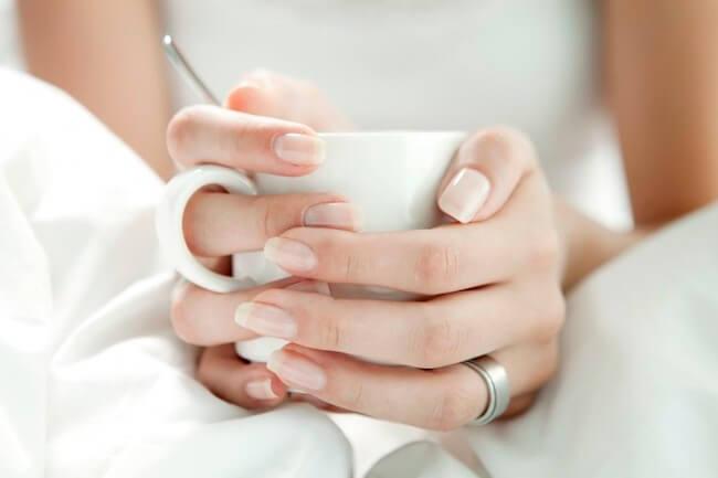 白いマグカップを持つ女性の手