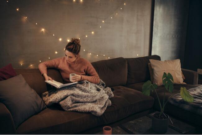 ソファーでマグカップ片手に読書する女性
