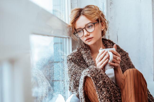 メガネをかけてマグカップを持ち窓の外を眺める女性