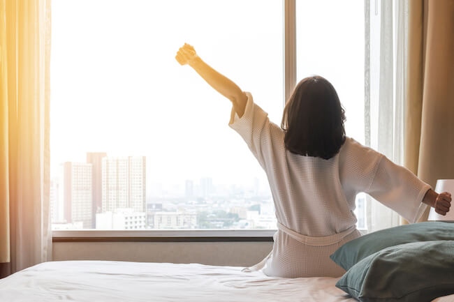 ベッドの上でカーテンを開けて伸びをする女性の後ろ姿