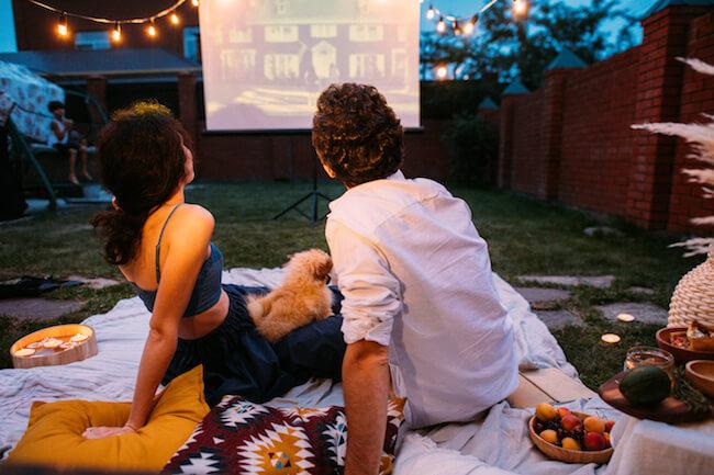 外で映画を見る男女