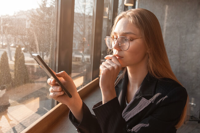 スマホを操作するメガネをかけた女性