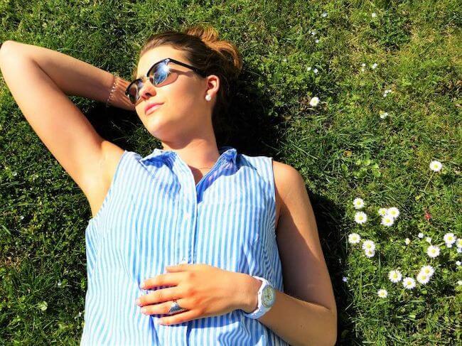 芝生に寝転がって日光浴をするサングラスをかけた女性