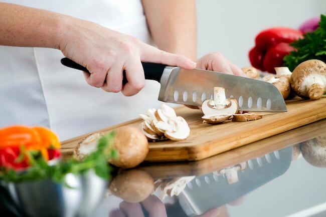 キノコを包丁で切る女性の手元