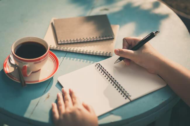 ノートに書く女性の手