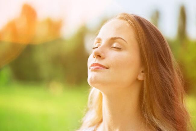 自然の中で目を閉じる女性