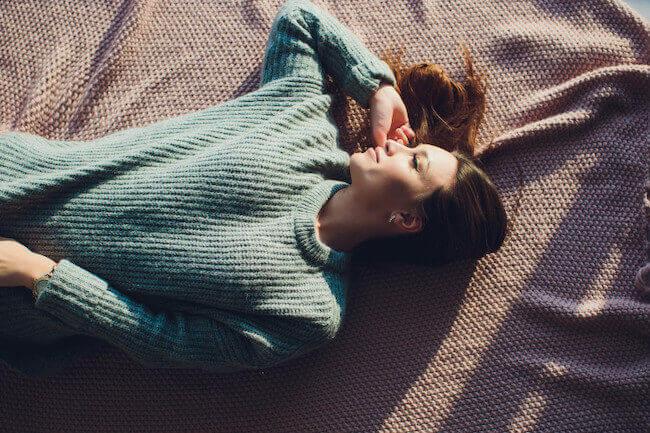 ニットを着て寝転ぶ女性