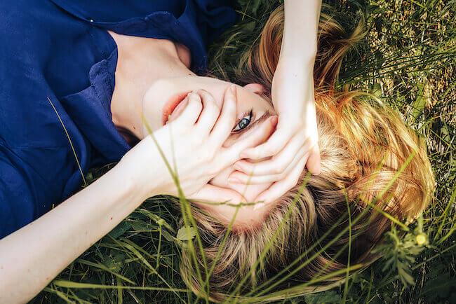 芝生の上に寝転ぶ女性